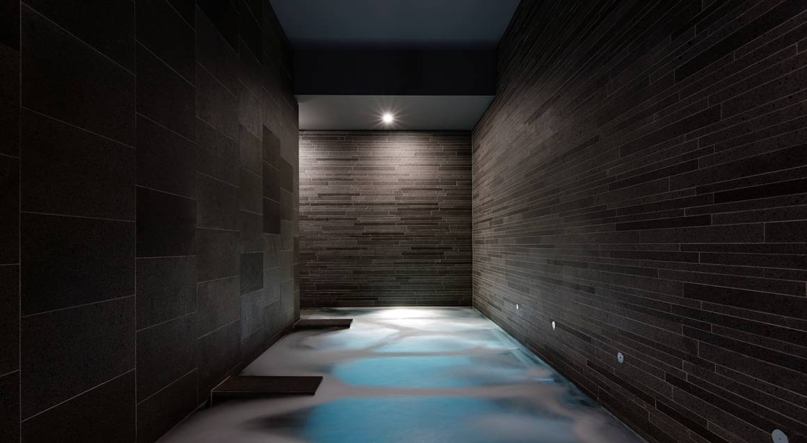 canberra hotel dim corridor with dark grey and brown walls and concrete floor with patches of blue decorating it