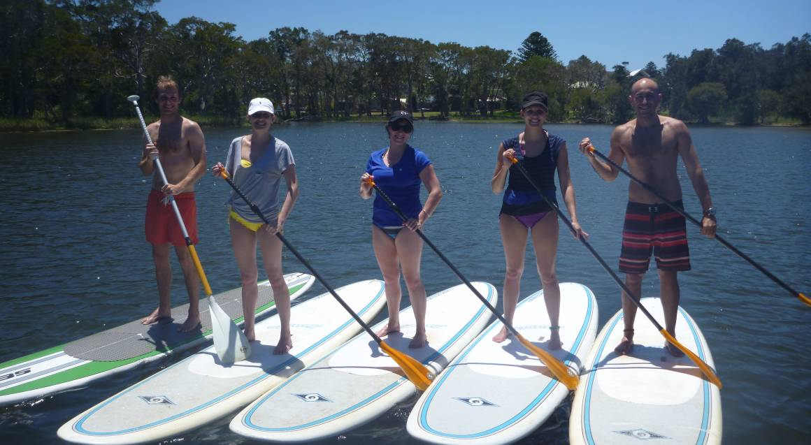 group on paddle boards in water standing together