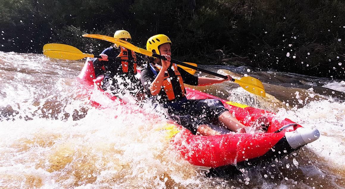 two people splashing through white water in a raft