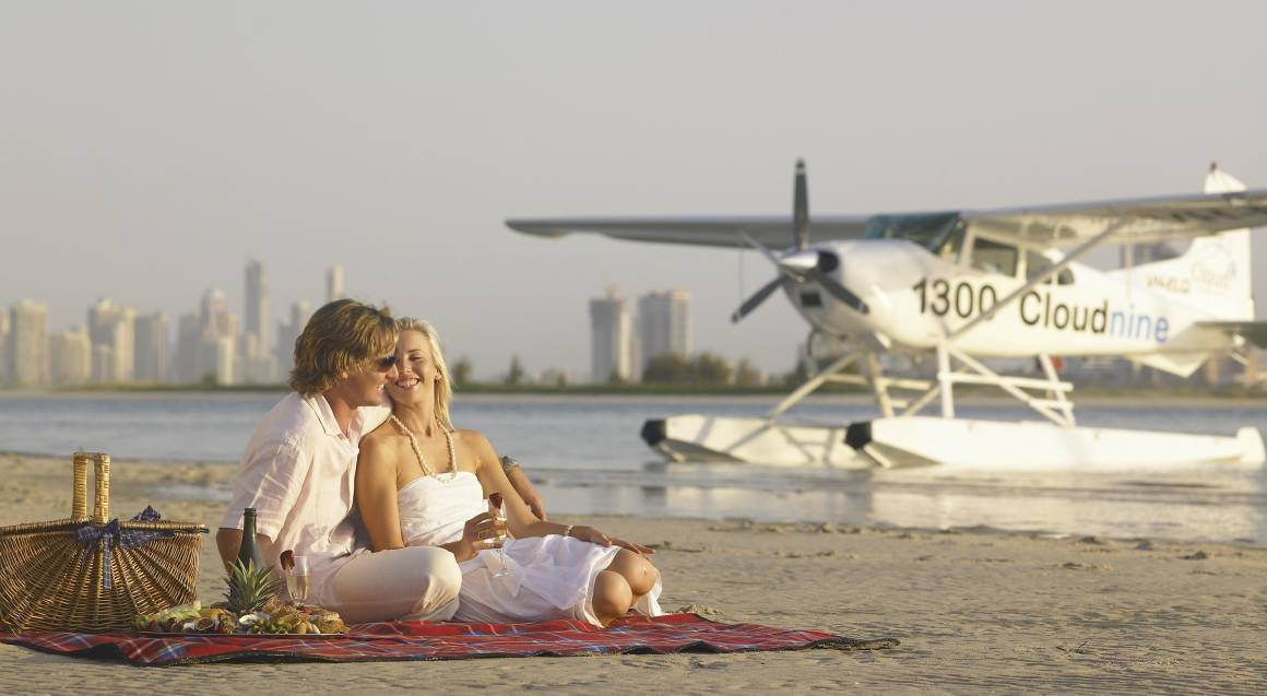 couple having seafood picnic on stradbroke island beach with seaplane