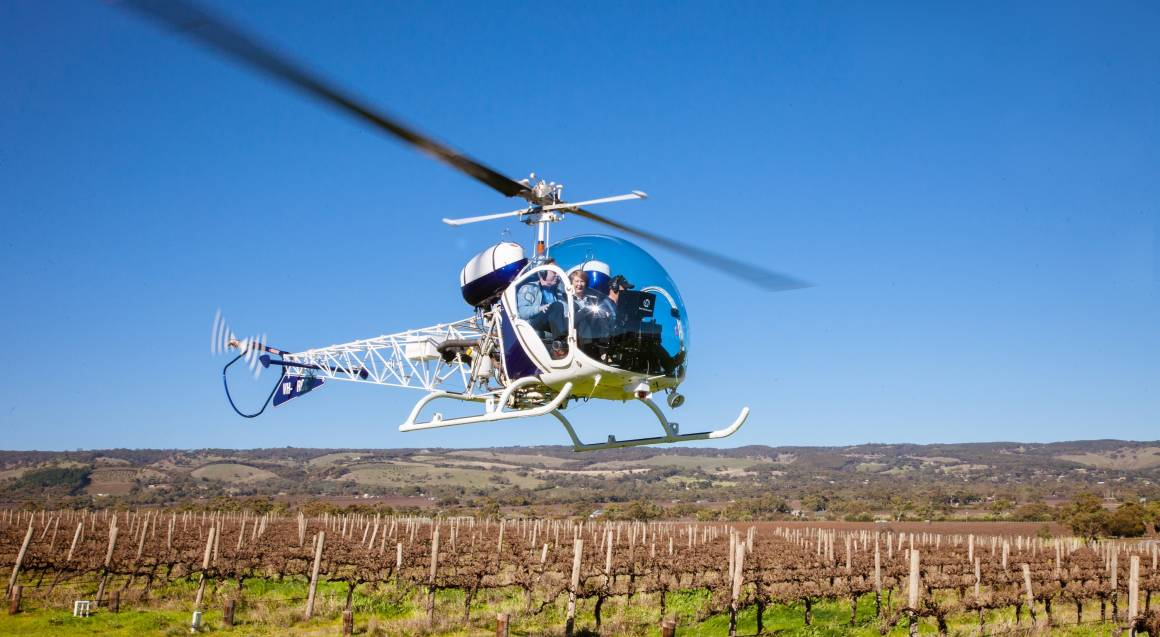 mclaren vale helicopter flight helicopter with a bubble windscreen with passenger and pilot in it hovering over a vineyard