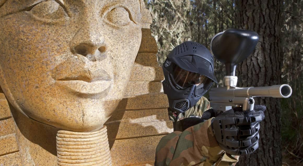man playing paintball aiming guns egyptian setting