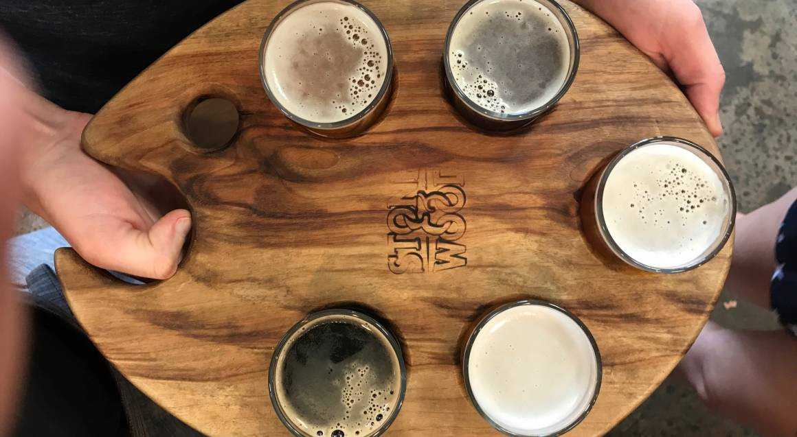 person holding beer tasting paddle stone and wood