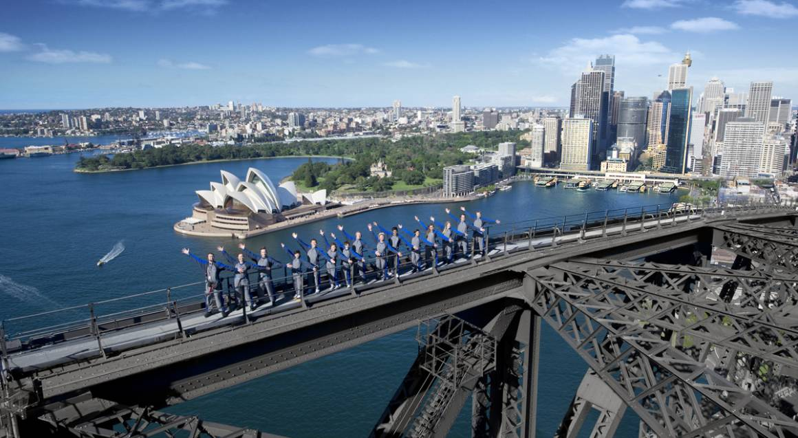 Line of people on the Sydney Harbour Bridge with Sydney aerial city skyline in the background
