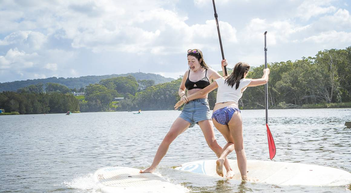 two young girls playing on paddle boards in the ocean