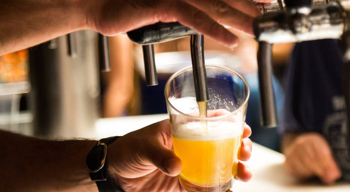 man pouring schooner of beer on tap