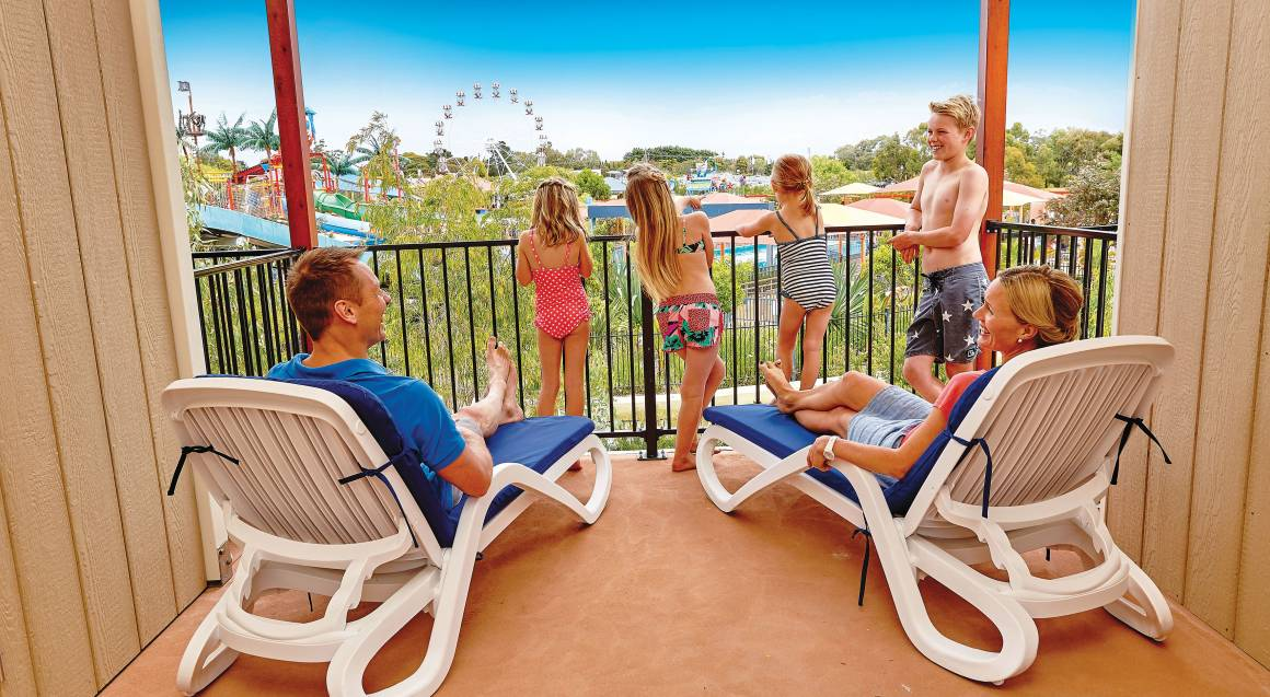 family relaxing in a cabana overlooking water park