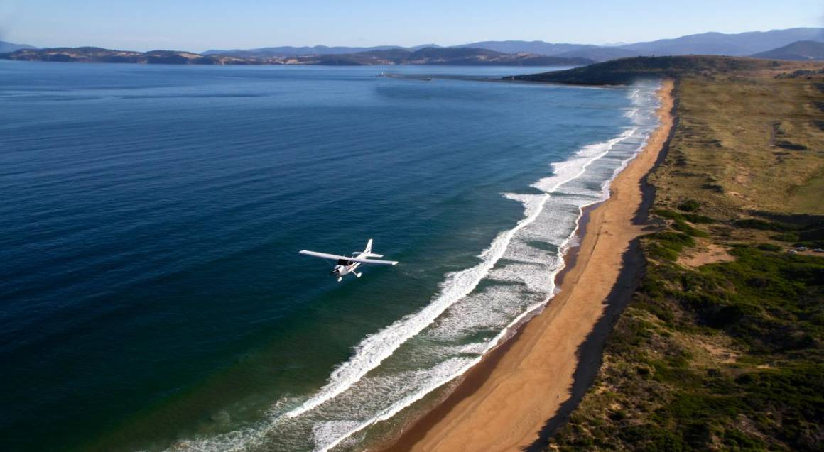 small white aeroplane flying over a beach
