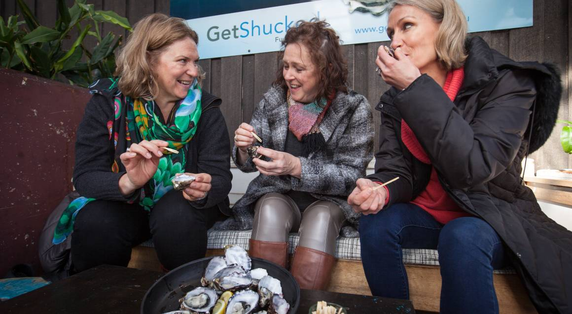 three women enjoying food samples on bruny island food tour