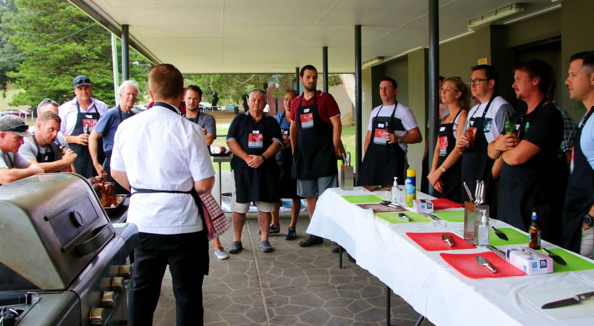 bbq cooking class students standing in a semicircle with aprons on to face the instructor who's back is to the camera the bbq is behind him