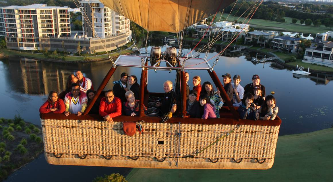 Group in hot air balloon flying over gold coast