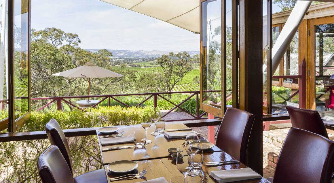 tables set at a restaurant overlooking a vineyard