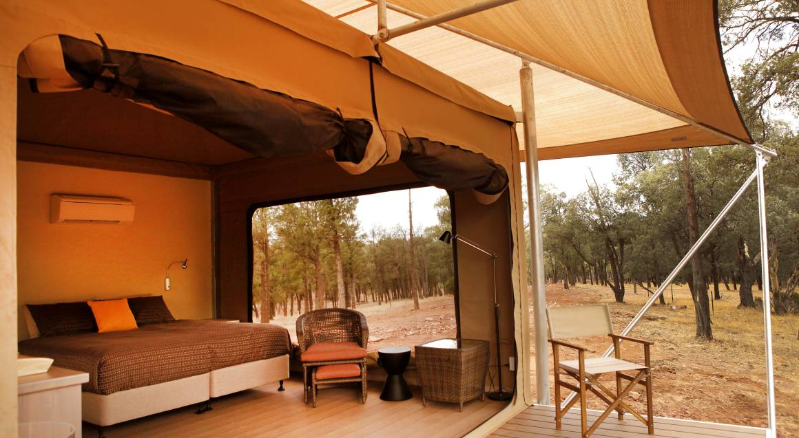 interior of glamping tent showing bed and chairs and outback in the distance