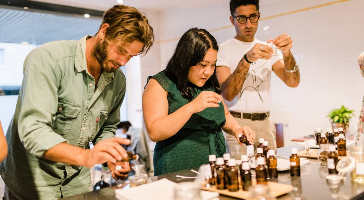 group of people mixing different fragrances in perfume workshop