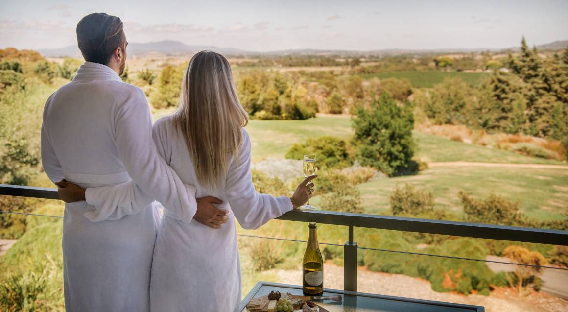 couple standing on a balcony overlooking yarra valley winery