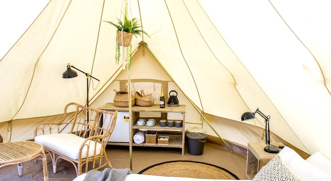 interior of tent with a bed fridge and chairs