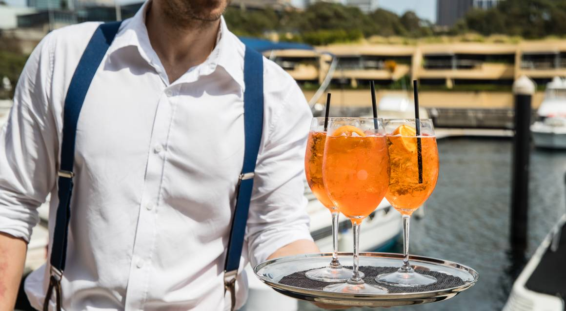 waiter holding tray of aperol spritz cocktail