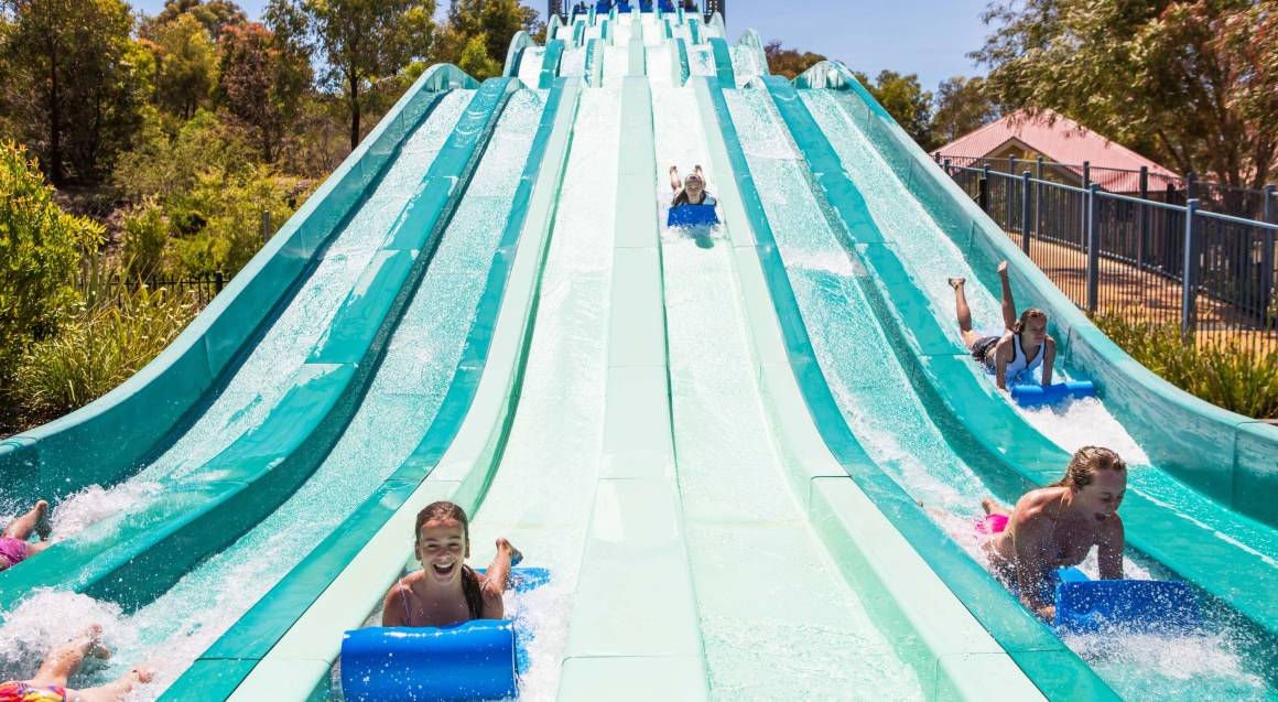 young girl sliding to the bottom of a large blue waterslide