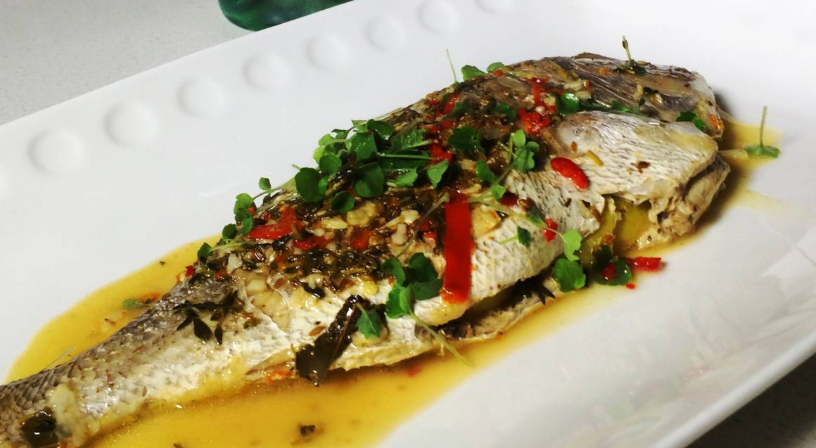 close up of a whole fish bbq with herbs as garnish sitting on a white plate in a pool of sauce
