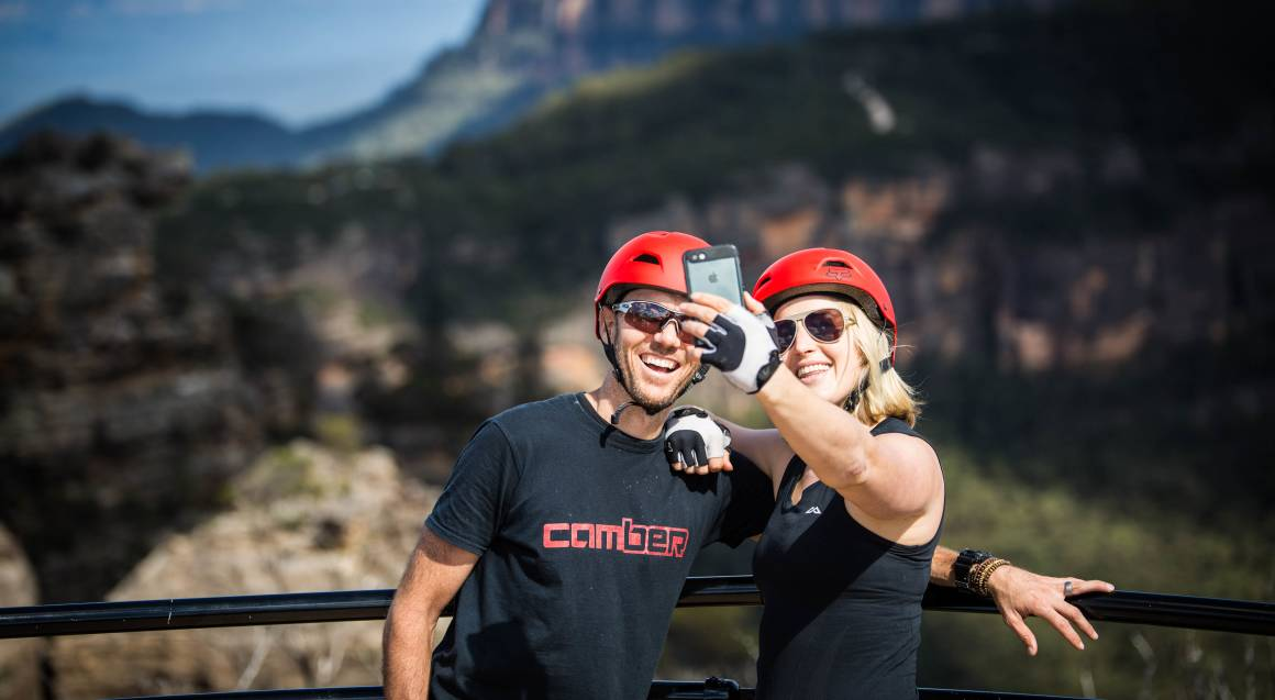 Mountain bike tour man and woman with red helmets and sunglasses on taking a selfie in front of a railing and a valley with bushland in the background