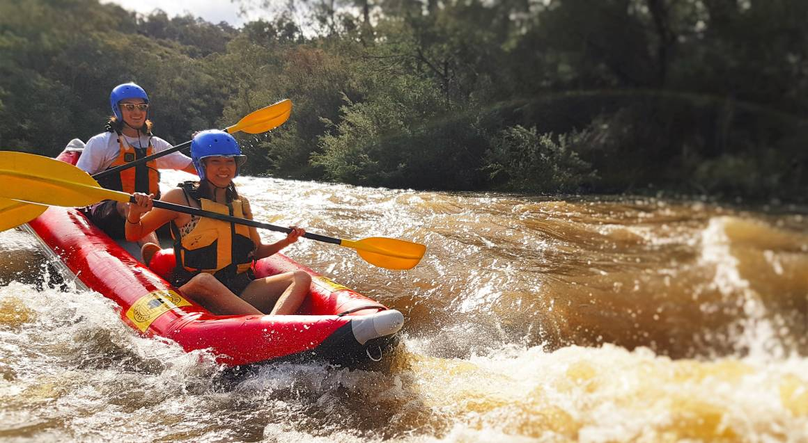 two people wearing helmets and lifejackets in a red raft paddling through white water on yarra river