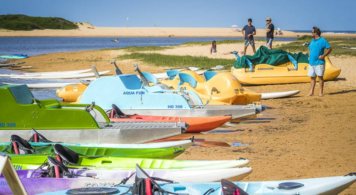 kayaks and pedal boats lined up on the beach