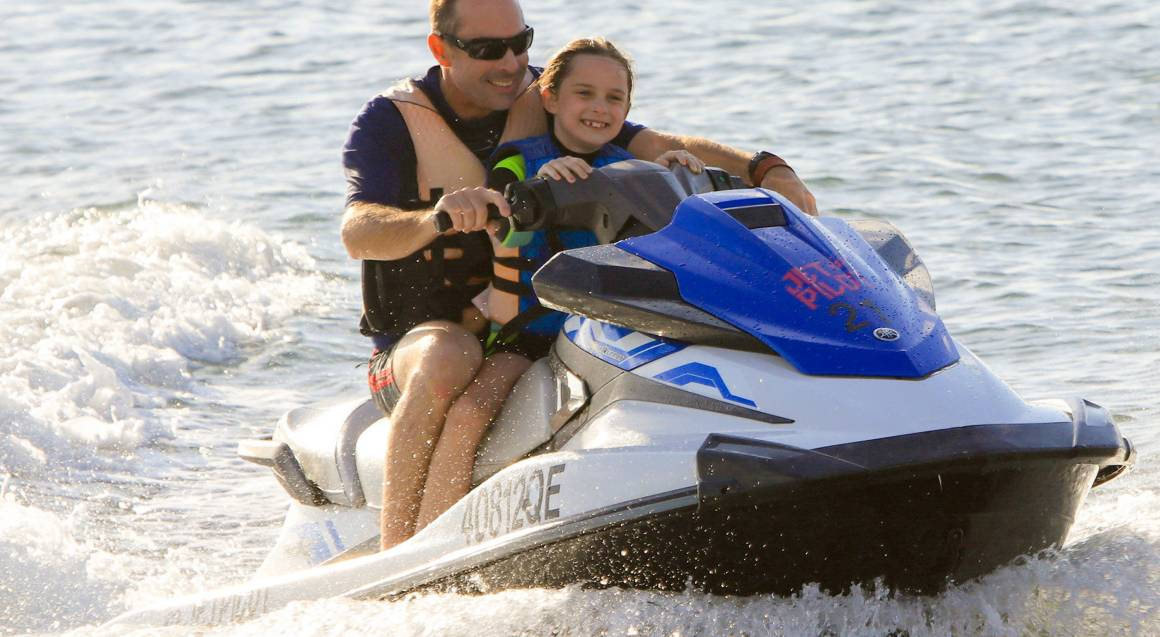 daughter and father riding jet ski in ocean