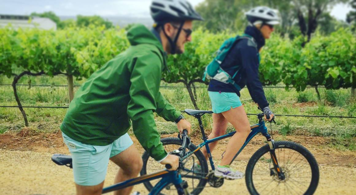 couple bike riding past mclaren vale vineyard