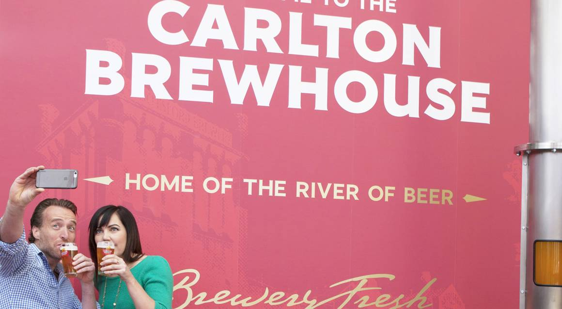 couple posing with beers outside carlton brewhouse