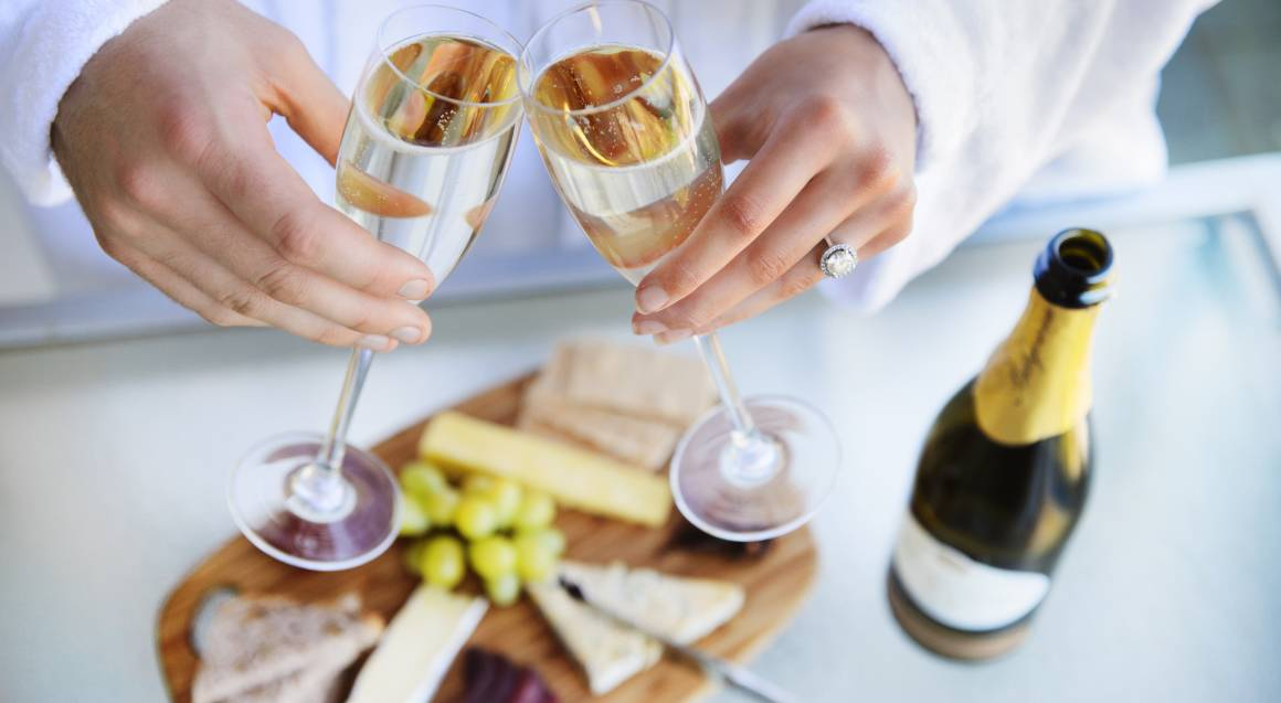 couple toasting two glasses of champagne with a cheese plate on the table