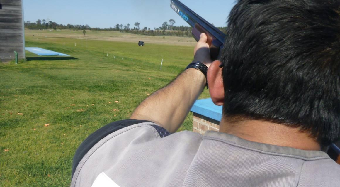 Hitting Targets clay target shooting with live ammo man aiming and shooting gun at target