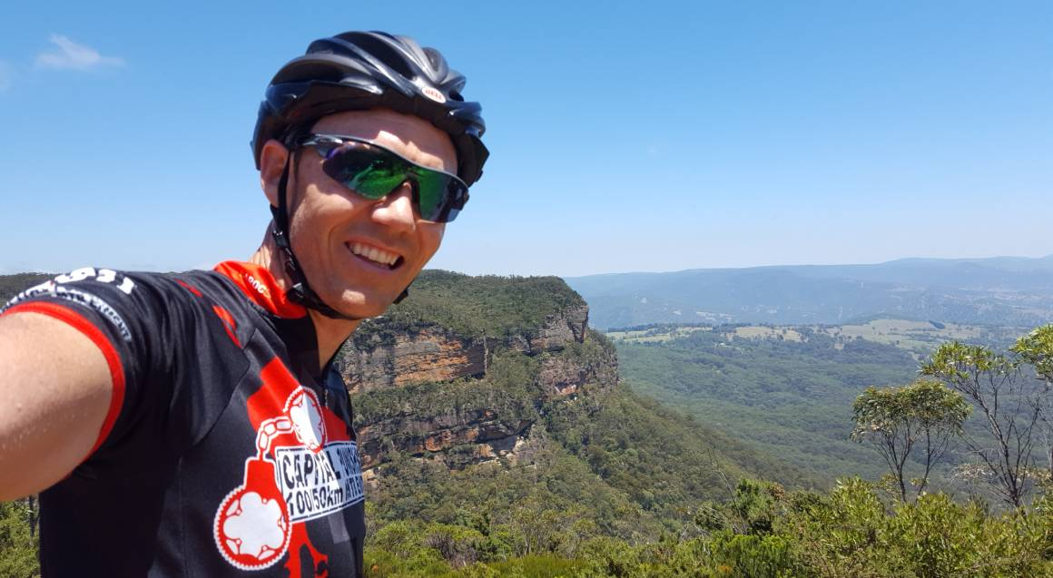 Mountain bike tour man with sunglasses and a bike helmet on with the bushland and mountains in the background his arm is stretched to one side as he is taking a selfie