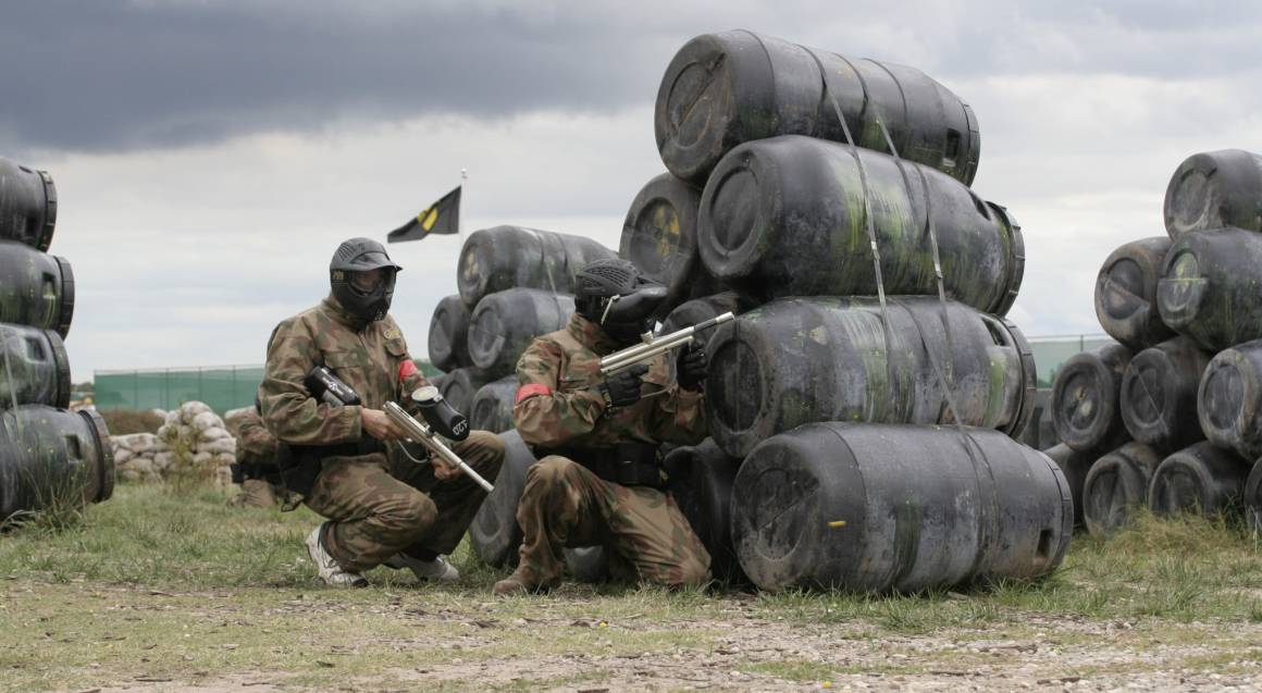 men playing paintball aiming guns