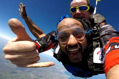 Two men jumping out of a plane while skydiving