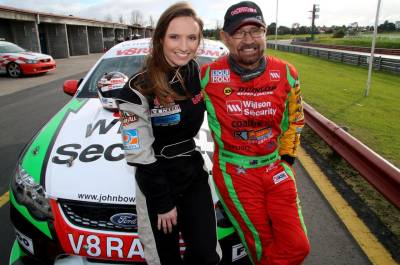 Man and women standing in front of a V8 supercar