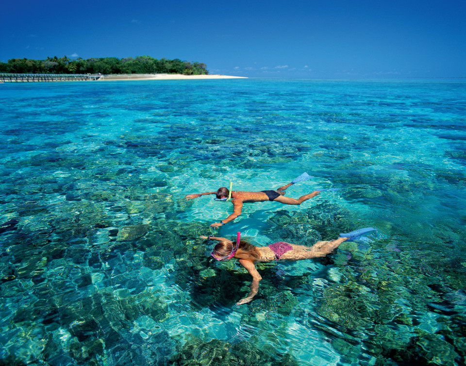 Two people snorkelling over the Great Barrier Reef