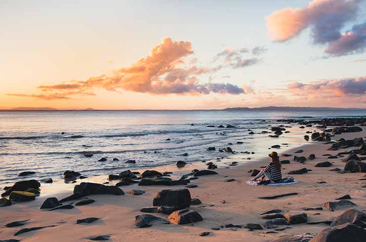 Woman sitting on the beach at Noosa Heads