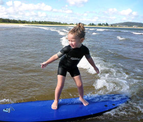 Little girl surfing wave in ocean shallows
