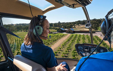 Woman in helicopter over wine region