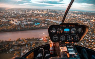 Helicopter flying over Brisbane at sunset