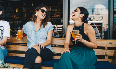 Two women drinking and laughing at a bar