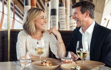 Woman and man eating meal and drinking wine in restaurant