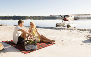 Man and woman having a picnic on the beach next to seaplane
