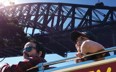 Couple on roofless bus in Sydney Harbour