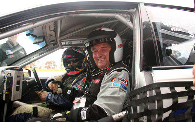 Man inside V8 race car with professional driver
