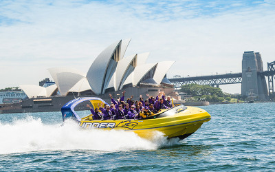Jet boat driving past Sydney Opera House and Harbour Bridge