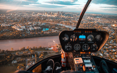 Helicopter flying over Brisbane at sunset