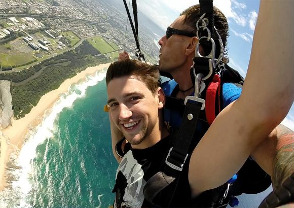 Man tandem skydiving over the beach