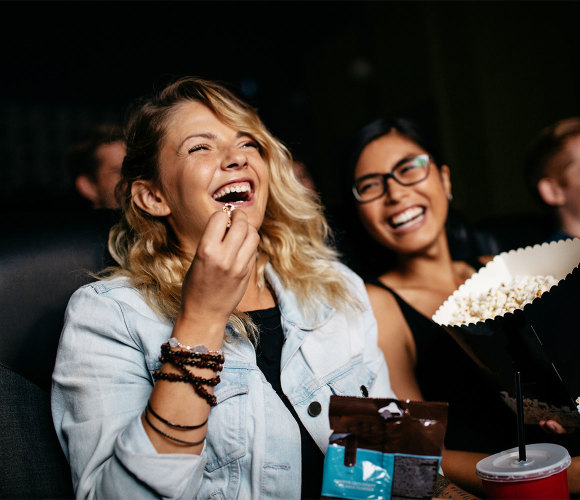 Women at the movies eating popcorn