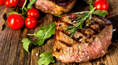 bbq cooking class grilled steak with back grill marks across it on wooden board styled with green herbs and cherry tomatoes